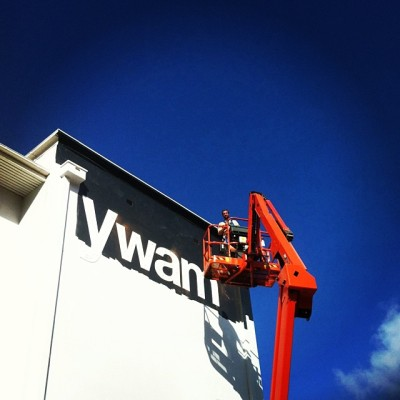 Ryan painting and installing signage at the city campus.